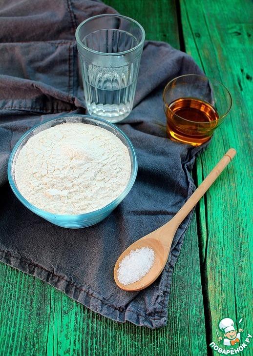 В миске смешайте просеянную муку и соль. Добавьте оливковое масло и воду, нагретую до 60-70 градусов. Замесите тесто.
