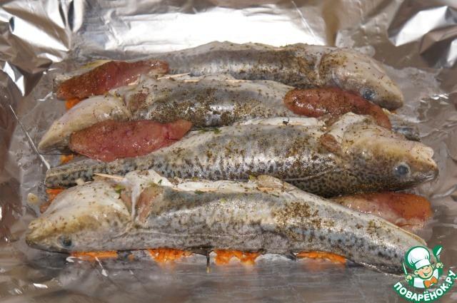 Большой кусок фольги смазать растительным маслом. На одну половину выложить ровным слоем половину морковно-луковой смеси. Сверху расположить нафаршированные рыбки. Накрыть рыбки оставшейся морковно-луковой смесью.