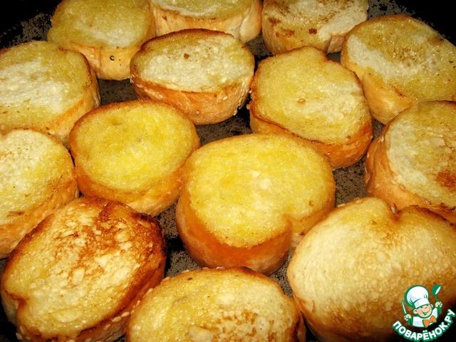 Багет нарезать на ломтики толщиной 1,5 см. Обжарить на сливочном масле с двух сторон до золотистого цвета.