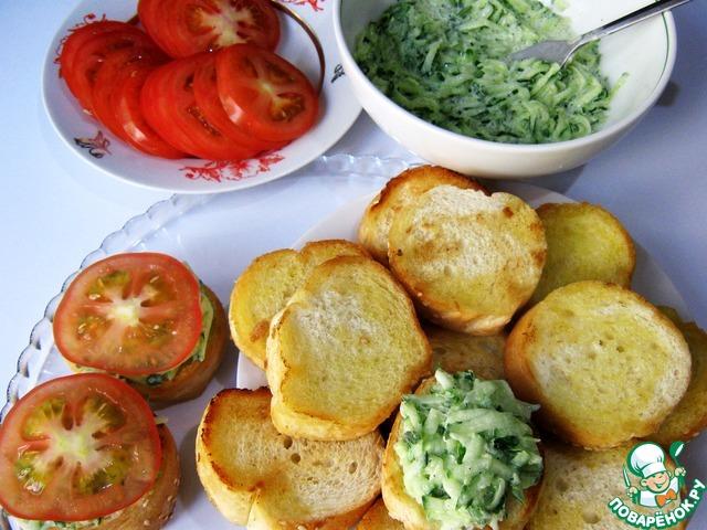 На ломтик багета выложить примерно столовую ложку начинки и ломтик помидора.