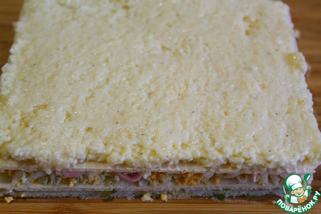 На яичный слой выкладываем следующий корж, смазываем его.   В сыр с чесноком добавляем 1ст л заправки перемешиваем и выкладываем ровным слоем на корж - отложенный сыр не используем!!!    Сырный слой смазываем растительным маслом чуть-чуть.