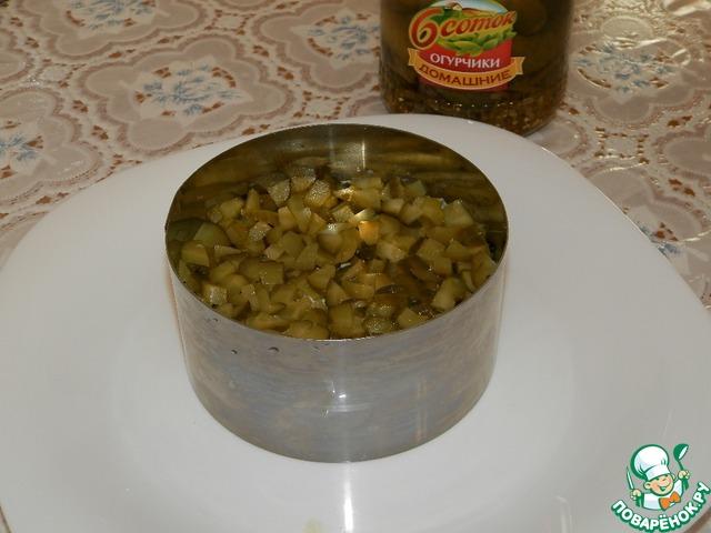 Огурцы маринованные порезать кубиками и выложить сверху на яйца. Прижать ложкой.