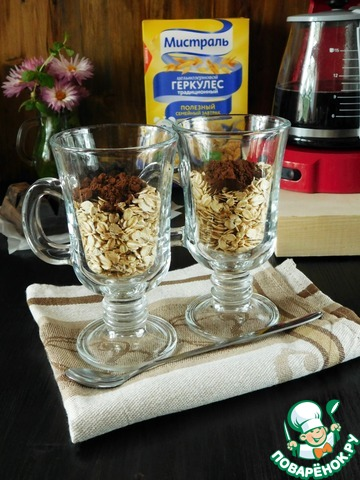Ингредиенты рассчитаны на 2 порции, соответственно, всё делим пополам.   В два стакана (или баночки) насыпаем равное количество геркулеса и какао-порошка. Добавляем шоколад, натертый на терке. Я использовала готовую кондитерскую крупку. Перемешиваем сухие ингредиенты.