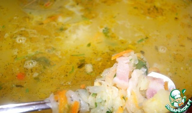 Лук нарезать и тушить в нагретом масле 2 минуты, добавить натертую морковь и тушить еще 2 минуты.    Бекон нарезать полосками и добавить к моркови и луку, обжарить. Ввести все в кипящий суп. Добавить лавровый лист, перец и зелень, варить 1-2 минуты и выключить огонь.