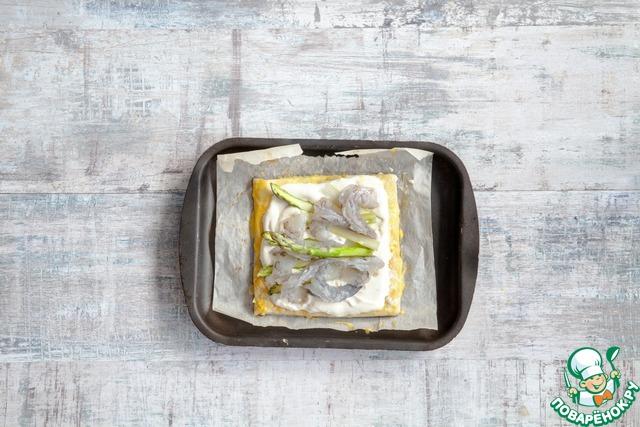 Когда тесто подпечется, выньте противень из духовки, быстро выложите в центр каждого квадрата заливку, в ней слегка утопите спаржу и креветки. Смажьте края теста смесью желтка и сливок. Верните тарты в духовку, запекайте до румяной корочки, примерно 20 мин. Подавайте теплыми.