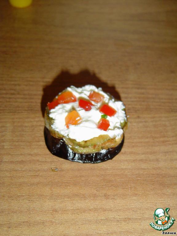 На баклажаны укладываем кружки кабачков, смазываем их творожным сыром и засыпаем зеленью и сладким перцем.