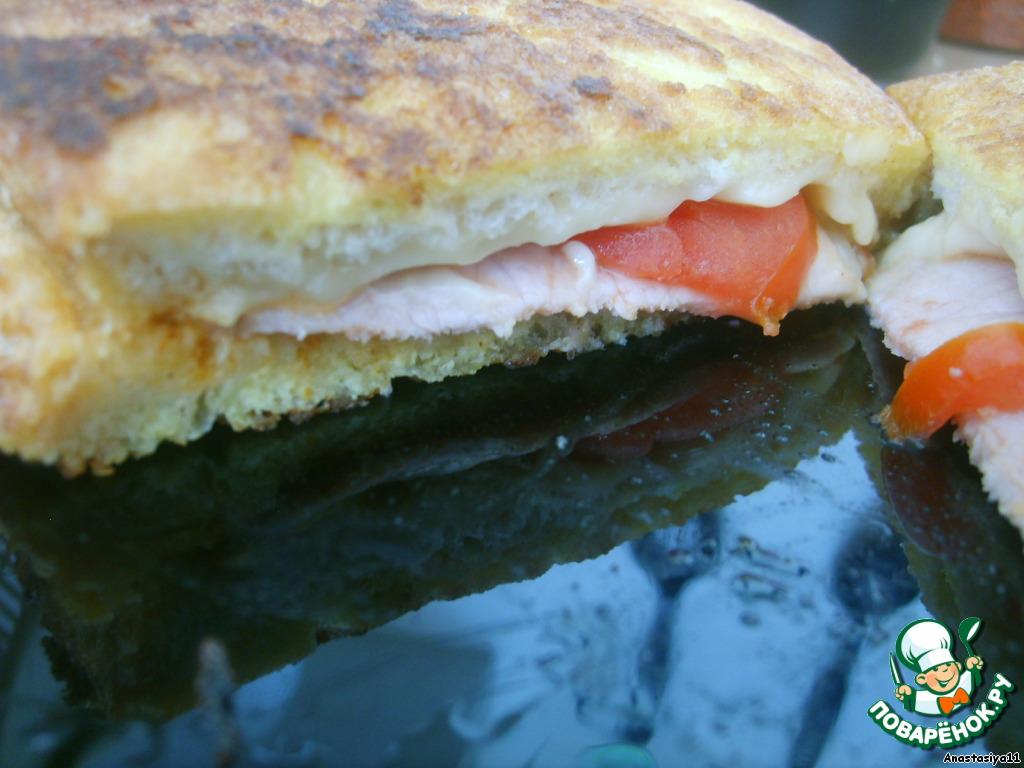 Хлеб смазать майонезом, посыпать зеленью и чесноком.   Сверху положить кусочек ветчины, сыра и помидора. Закрыть вторым кусочком хлеба.        Яйцо слегка взбить венчиком. Обмакнуть бутерброд в яйцо и обжарить на растительном масле до подрумянивания.
