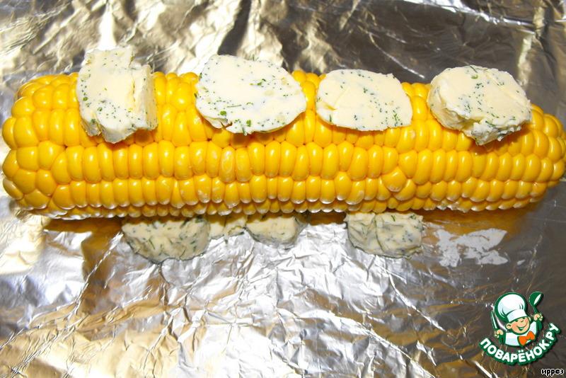 Вынуть масло и нарезать на кусочки.    Разрезать, при необходимости, каждый початок пополам.    Разогреть духовку до максимальной температуры.    Выложить кукурузу в фольгу, положить на дно кусочки масла и выложить также масло поверх початков.