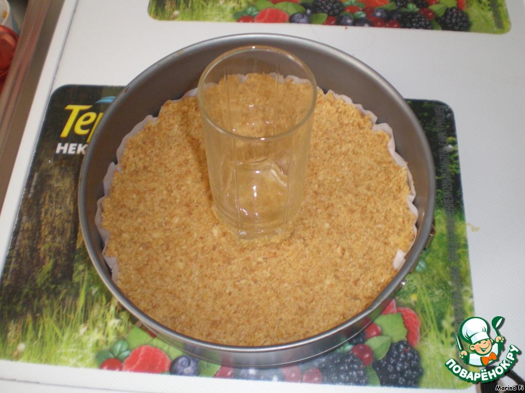 Печенье смешать с растопленным сливочным маслом, выложить в форму на пергамент и, хорошо утрамбовав, отправить в холодильник.