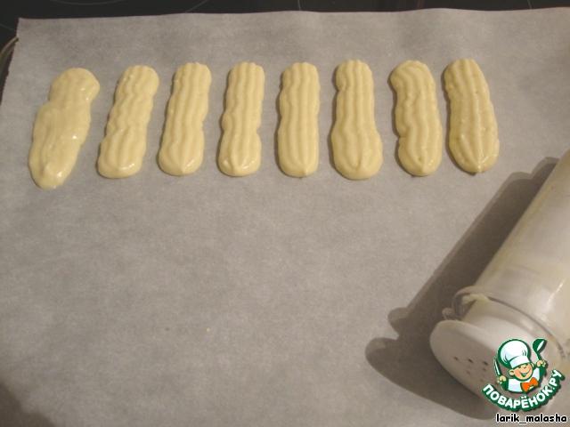 Из кондитерского шприца или пакета с вырезанным уголочком сделать печенье длинной около 7 см и шириной 3 см. Выкладывать на противень, покрытой бумагой для выпечки.   Не делайте моей ошибки: я выкладывала печенье очень близко друг к другу, при выпечке печенье слиплось. Поэтому оставляйте побольше расстояния между печеньем.