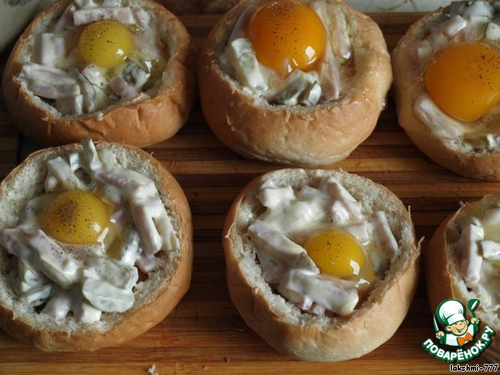 """Углубления булочек смачиваем молоком (по половине столовой ложки) и смазываем сливочным маслом. Я масло разрезала на 6 кусочков и смазала внутри каждую булочку. Выкладываем начинку, посыпаем зеленью и выпускаем по яйцу в каждую булочку. После двух попыток выпустить куриные яйца, я заменила их на перепелиные. Всё-таки, для этой цели булочки должны быть побольше или же меньше начинки класть. Белок всё время пытался """"убежать"""". Желтки посыпаем чёрным молотым перцем."""