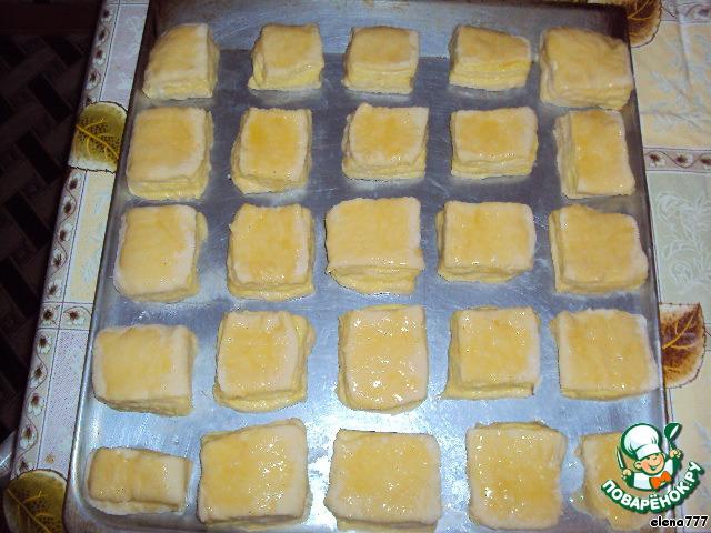 Выложить квадраты на смазанный противень и обмазать верх вот такой смесью: растереть один желток с 3ч. л. сахара и 1ч. л. растительного масла без запаха.