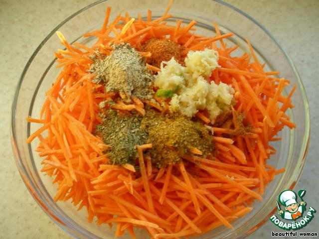 Морковь натираем на тёрке для приготовления корейских салатов, добавляем чеснок пропущенный через чесночницу, молотый перец чили, молотый имбирь, приправы для рыбы, курицы, корейской моркови, хмели-сунели и выливаем оставшееся оливковое масло на специи. Перемнём морковь руками, оставим на 5 минут.