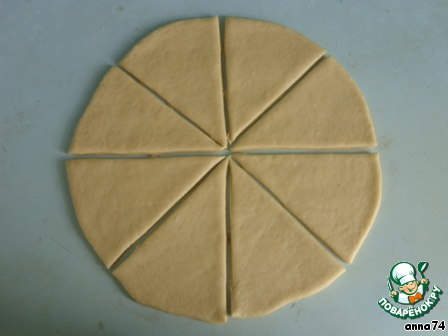 Разделить тесто на 3 части. Из каждой части раскатать круг толщиной около 5 мм, разрезать его на 8 частей, как показано на фотографии. Муку подсыпать не нужно, тесто не липнет.