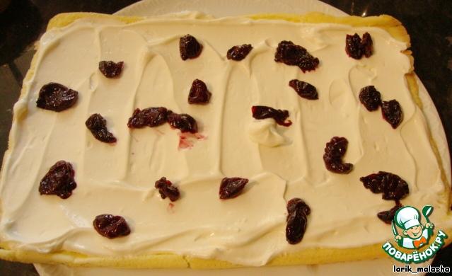 Замороженные ягоды положить в катрюлю, засыпать сахаром (2 ст. л.) и варить на небольшом огне около 15 минут. Ягоды разморозятся, пустят сок, получается что-то вроде жидкого варенья. Полученный сок слить (его можно будет куда-нибудь использовать), а ягоды оставить для начинки.       Когда бисквит будет готов, вынуть горячим из духовки, снять бумагу и сразу же завернуть в полотенце. Дать остыть.        Когда корж остынет, развернуть рулет, смазать кремом (немного оставить на украшение), сверху уложить вишню.