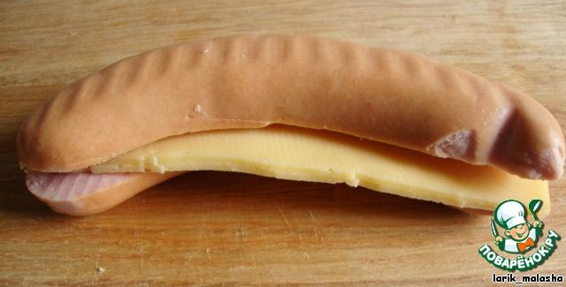 Сыр нарезать тонкими пластинками, вложить в колбаску.