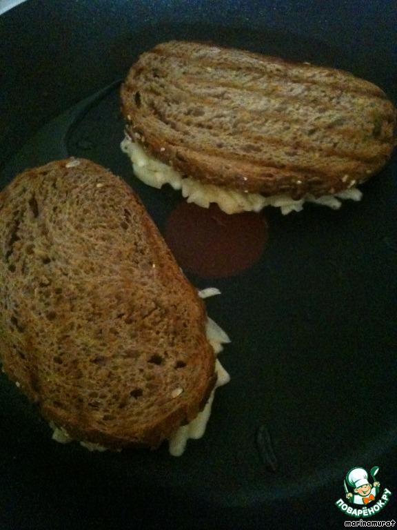На сковороде разогреваем 1 ст. л. масла и кладем бутерброды начинкой вниз.