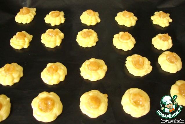 """Тщательное размешать, чтобы получить мягкое однородное тесто. Выложить тесто в кондитерский мешок или шприц с насадкой """"звездочка"""", сделать небольшие печенья на противне, застеленном бумагой для выпечки.    В центре печенья сделать небольшое углубление. Выложить начинку (смешать крахмал и варенье). Крахмал нужен для того, чтобы варенье хорошо застыло в готовом виде.        Выпекать в разогретой духовке 200 градусов около 12 минут (смотреть по своей духовке). Печенье должно слегка зарумяниться.    Охладить на противне, подавать."""