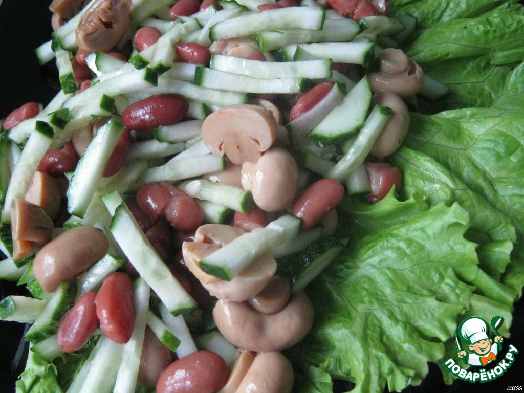 На сервировочную тарелку выкладываю листья салата, сверху грибы, фасоль и огурец.