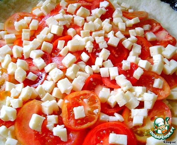 В смазанную форму выкладываем тесто, распределяем его по всей поверхности и поднимаем на бортики. Надо учитывать, что томаты дадут сок + еще место потребуется для заливки. Выкладываем примерно половину брынзы, на нее - томаты, снова брынзу.