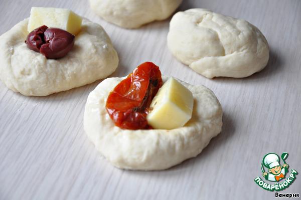 Разогреть духовку до 180 градусов.   Разделить тесто на 15-16 частей.    Сформировать шарики и в каждый шарик положить маслину и кубик сыра или вяленые томаты и сыр.