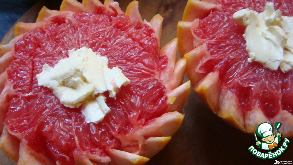 Серединку каждого грейпфрута начинить сливочным маслом и разложить его сверху.