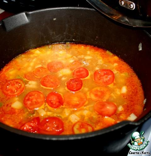 Спустя 10 минут добавляем, нарезанные кружками помидоры, доливаем воду так, чтобы она полностью покрыла все продукты и тушим на медленном огне около 15 минут.