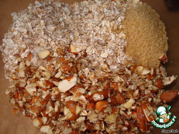 В другой чашке соединить овсяные хлопья, хлопья 5 злаков, миндаль, грецкий орех, нарезанный на кусочки, соль, коричневый сахар.
