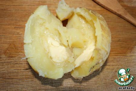 Мякоть картошки частично выскребаем ложечкой и кладем на обе половинки кусочек сливочного масла, при желании солим картошку.