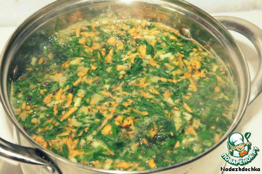 Когда картофель закипит, кидаем в кастрюлю зелень, морковь и перец. Укроп, петрушку и зеленый лук оставляем на потом. Томить на медленном огне до готовности картофеля