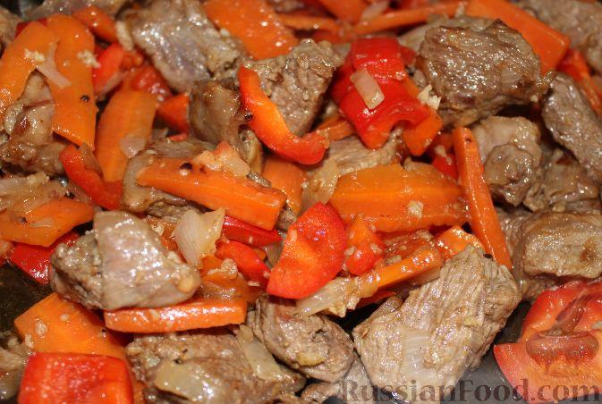 Добавить к мясу сладкий перец, жарить мясо и овощи еще пять минут.  Добавить чеснок, жарить около 1 минуты.