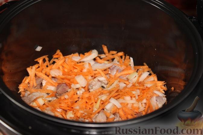 Налить в чашу мультиварки растительное масло, через минуту выложить мясо, морковь и лук.