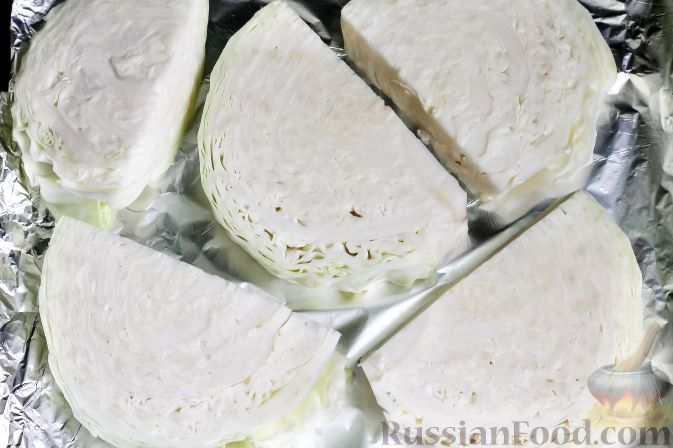 Как приготовить запеченную капусту под сырным соусом, с беконом:     С вилка капусты счистите верхние листья, промойте в воде, разрежьте пополам и каждую половинку нарежьте ломтями. Смажьте противень или фольгу растительным маслом и выложите на них капустные ломтики. Присолите и поперчите. Запеките около 25-30 минут при 180 градусах в духовке.