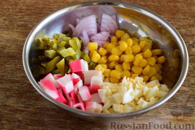 Выкладываем все ингредиенты салата в миску, с консервированной кукурузы сливаем жидкость и добавляем ее в салат.
