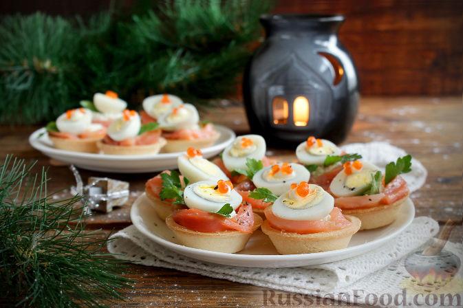 Сверху украшаем листиком петрушки и половинкой перепелиного яйца, по желанию каплей майонеза крепим по две-три икринки, присыпаем черным перцем — праздничные тарталетки готовы. Приятного аппетита!