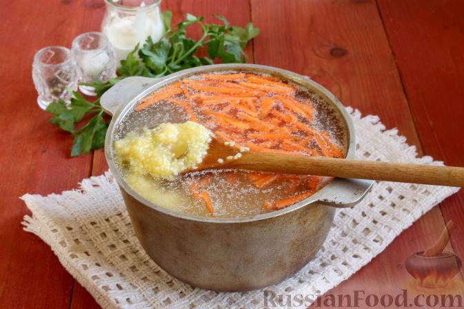 Добавляем подготовленную кукурузную крупу и варим суп, помешивая, при умеренном кипении до мягкости моркови и крупы.   (Чтобы кукурузная крупа быстрее разварилась, ее можно предварительно замочить в холодной воде на несколько часов.)