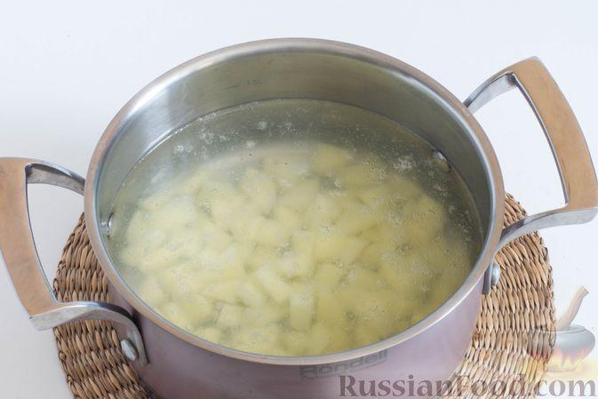 Налейте воду в кастрюлю и доведите до кипения.   Картофель очистите, нарежьте небольшими кубиками и отправьте в кипящую воду.