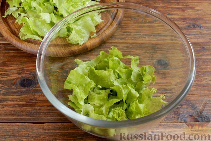 На дно прозрачного салатника выкладываем половину салатных листьев.